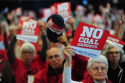 People against coal exports hold up signs during the Longview Coal Exports Hearing. (Power Past Coal / Alex Milan Tracey)